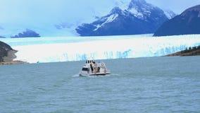 White ship running in front of Perito Moreno Glacier stock video footage