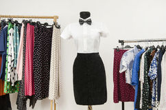 White shirt with bowtie and a black skirt on a mannequin. Wardrobe with polka dots clothes. Stock Image