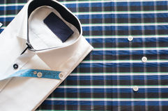 White shirt on chequered background with measuring tape. White shirt on chequered background. with measuring tape and buttons, showing tailoring Royalty Free Stock Photo