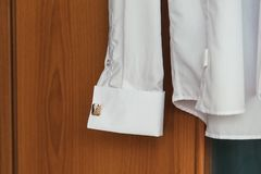 White shirt with a cufflink on the sleeve on a wooden background. White shirt with a cufflink on the sleeve on a wooden cupboard stock photography