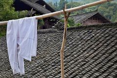 A white shirt in the foreground of a small village of  ethnic minority Miao hidden in the middle of nowhere in Hunan province. A white shirt in the foreground of Royalty Free Stock Image