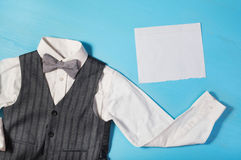White shirt, gray vest and a bow tie on a bright blue background Royalty Free Stock Photography