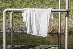White shirt hanging to dry. White shirt hanging over an aluminum pipe to dry royalty free stock images
