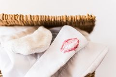White shirt with lipstick smear. White shirt with lipstick imprint on its collar hanging off laundry basket - suggestion of infidelity Stock Photo