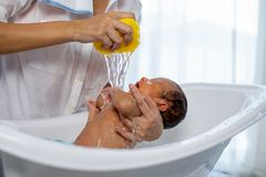 White shirt mother use yellow sponge to bath little newborn baby in white bathtub royalty free stock photography