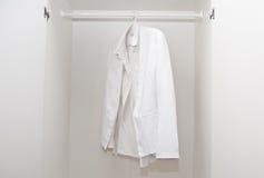 White shirt in wardrobe. White shirt and jacket in white wardrobe Royalty Free Stock Image