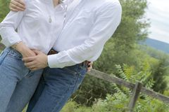 White Shirts and Blue Jeans. A couple in crisp white shirts and faded jeans, holding hands and hugging. Greenery in the background. Picture at a slant. Couple stock photography
