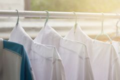 Shirts hanging on on open rail or clothes outdoors on laundry day. royalty free stock photo