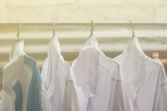Shirts hanging on on open rail or clothes outdoors on laundry day. stock photos