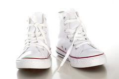 White Shoe. White sport style shoe in front of white background Stock Photography