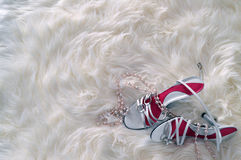 White shoe and beads. A pair of white shoes and beads on fluffy fur rug Royalty Free Stock Image