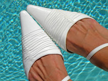 White shoes. A pair of elegant white shoes pictured against blue water Royalty Free Stock Photos