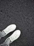 White shoes on asphalt. Contrasty image of shoes in rainy day Stock Photos