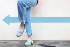 White shoes concept. Female wearing white sneakers with blue arrows line direction on concrete road background Stock Images