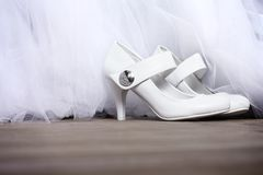 White shoes with crystals. Pair of white wedding shoes on the floor in front of wedding dress Stock Photo