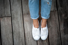 White shoes,Fashion woman`s legs with sneakers seated on Wooden floor Royalty Free Stock Photo