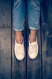 White shoes,Fashion woman`s legs with sneakers seated on Wooden floor Stock Image
