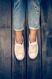 White shoes,Fashion woman`s legs with sneakers seated on Wooden floor Stock Photo
