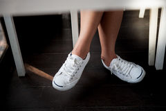 White shoes,Fashion woman`s legs with sneakers seated on Wooden floor Stock Images