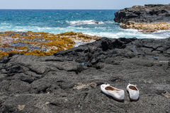 White shoes on lava rock at beach in Hawaii. White shoes left in Hawaii on black lava rock Stock Photo