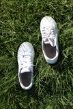 White shoes placed in step on the green grass stock photos