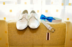 White shoes and strap. And a blue bow tie (bowtie royalty free stock photos