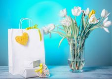 Image of bargain sale on spring season or Valentines day. White shopping paper bags with yellow heart, gifts and bouquet of fresh white tulips on on a gentle stock photography