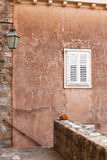 White shutters on aged wall small lamp and cat. White window shutters on brown aged wall, with a small lamp and a cat standing on the edge in Dubrovnik, Croatia royalty free stock photography