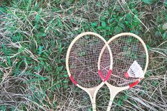 White shuttlecock and badminton racket lying on green grass stock photos
