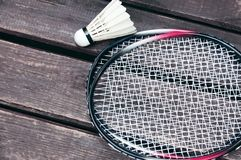 White shuttlecock and badminton rackets. Lie on a wooden background Royalty Free Stock Images