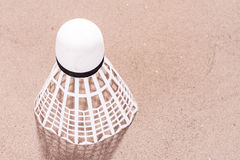 White shuttlecock in the sand. At the beach Royalty Free Stock Photography