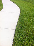 White Sidewalk Edged with Grass Stock Photo