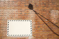 White sign on brick wall with lamp shadow. On a sunny day Stock Photo