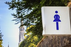 White sign indicating the entrance to the women`s washroom Royalty Free Stock Photography