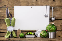 White sign on old wooden background decorated with silver cutler. White sign on rustic wooden background decorated with silver cutlery, dishes and green Royalty Free Stock Images