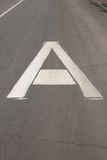 """The white sign on the road """"Bus lane"""" in the form of a big capital letter A.  Stock Photography"""