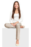 White sign woman sitting on billboard. Sign people. Woman sitting on blank billboard placard sign. Casual young beautiful multiracial Asian isolated on white stock image
