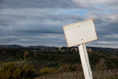 White sign on wooden pole. And Tuscan landscape stock image