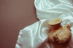 White silk with ancient vase. Curvy white silk drapery on dark background Royalty Free Stock Image