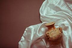 White silk with ancient vase. Curvy white silk drapery on dark background Stock Photo