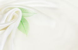 White silk background with flower drapery. And green leaves Royalty Free Stock Photography