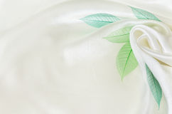 White silk background with flower drapery. And green leaves Stock Photography