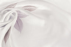 White silk background with flower drapery. And leaves Royalty Free Stock Photography