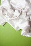 White silk background on green. Curvy white silk drapery on dark background Stock Image