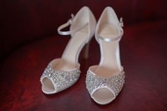 White silk bridal peep toe shoes with rhinestones and delicate beads, displayed fully, in pair, on a dark red Stock Photo