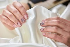 White silk in female manicured hands. Stock Images