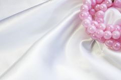 White silk with pink pearls. White atlas with pink pearls Royalty Free Stock Image