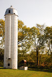 White Silo. This is a shot of a white silo next to a tree line Royalty Free Stock Photo