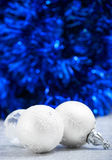 White and silver christmas balls on dark blue bokeh background with space for text. Merry christmas card. Xmas Stock Photo