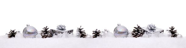 White and silver christmas balls with xmas present gift boxes in a row isolated on snow royalty free stock images